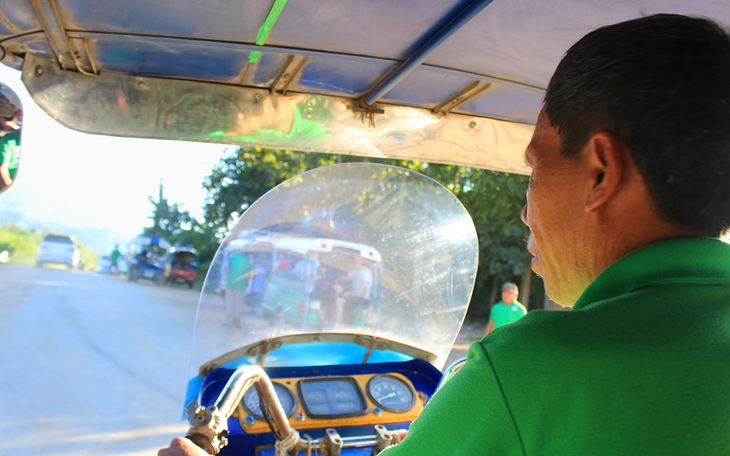 A tuk tuk rider in a green shirt driving to Luang Prabang in Laos.
