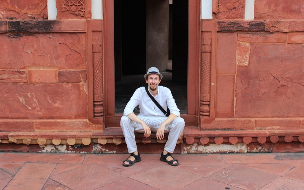 Arimo Koo sitting on steps of Agra Fort, India.