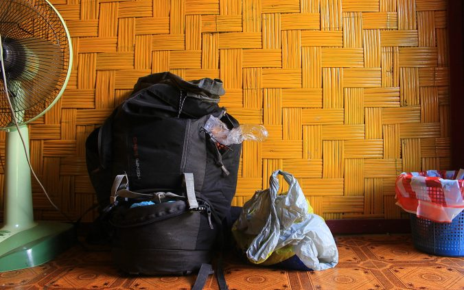 Most useful things to pack for a trip around the world. A black McKinley 65+10 liter backpack in a hostel room.