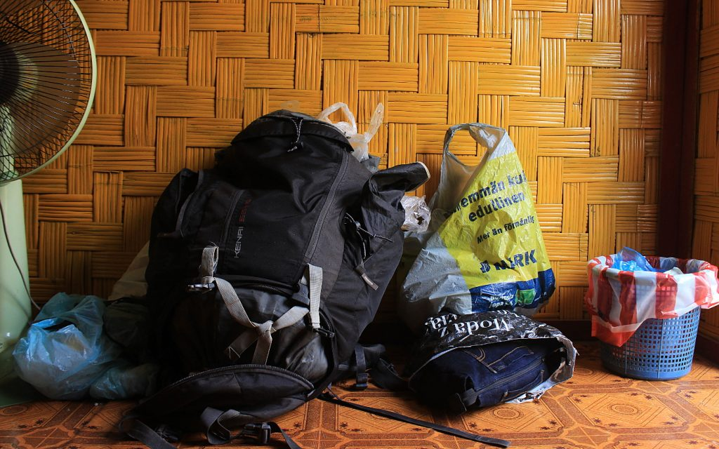 Best Travel Tips for Long-Term. A backpack and plastic bags in a hostel.