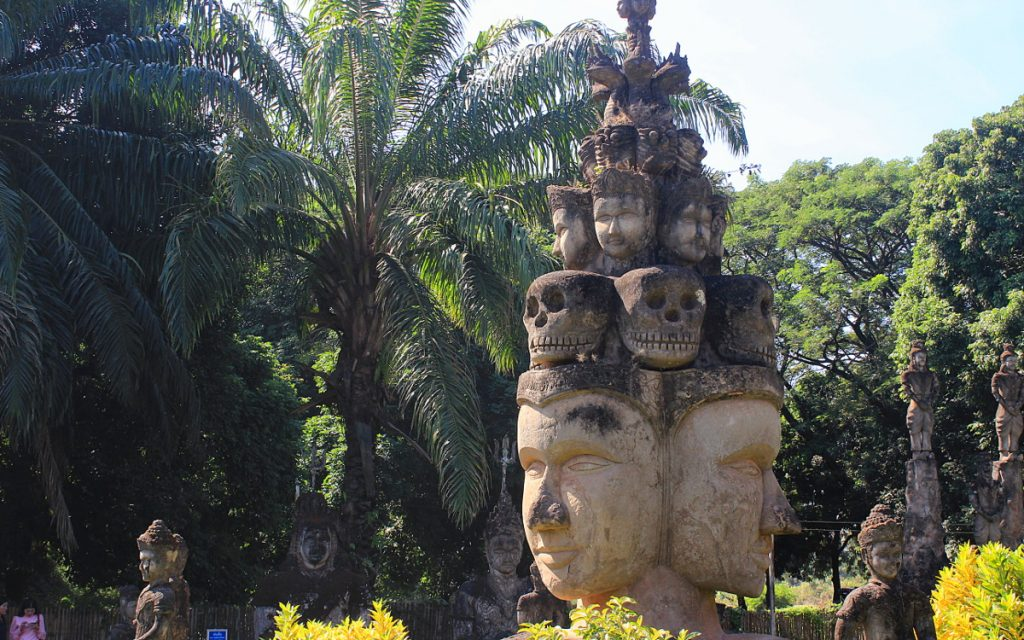 A totem statue of skulls and gods with a palm tree in the background.