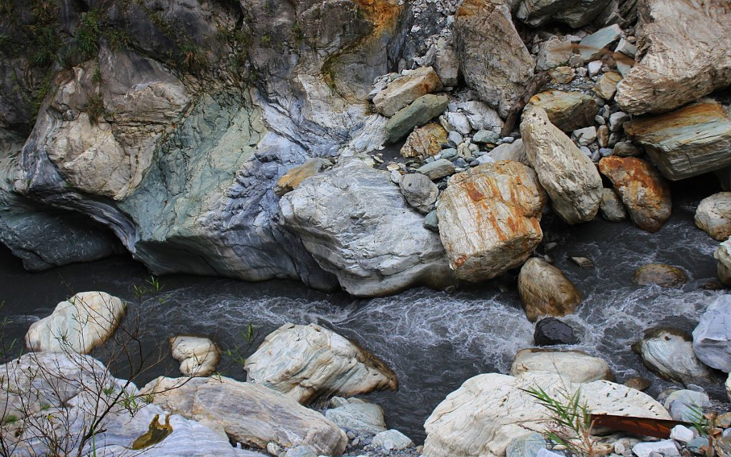 A stream in Taroko National Park with colorful rocks around it.