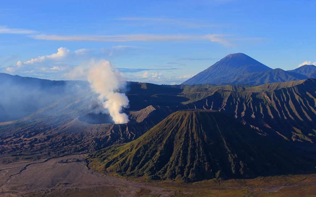 Mount Bromo (2392m) is the smoking crater on the left. The mountain in the front is Batok (2440m), while Java's highest mountain Mount Semeru (3676m) looms in the background.
