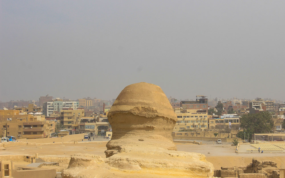 The Sphinx of Giza from behind with heavy smog in the background.