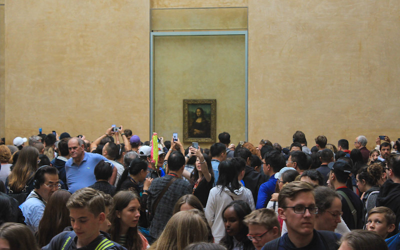 Crowds surround Mona Lisa in Louvre, Paris.
